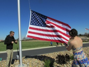 Gunners Mate 3/c David Hess and Aviation Ordinanceman Elizabeth Flemming, both of the USS Essex (LPH 2), hoist a brand new flag into place on the Avenue of Flags at Miramar National Cemetery.